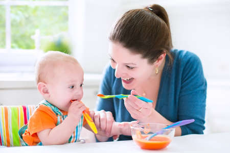 Young attractive mother feeding her cute baby son, giving him his first solid food, healthy vegetable pure from carrot with a plastic spoon sitting in a white sunny kitchen at a window at home photo