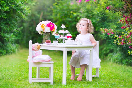 Adorable toddler girl with curly hair wearing a colorful dress on her birthday playing tea party with a teddy bear doll, toy dishes, cup cakes and muffins in a sunny summer garden Archivio Fotografico