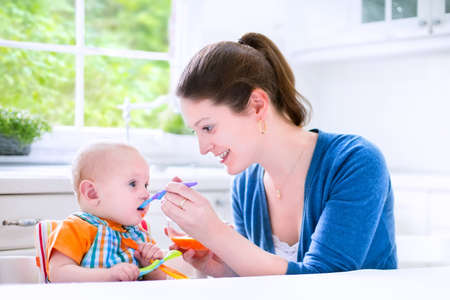 solid food: Young attractive mother feeding her cute baby son, giving him his first solid food, healthy vegetable pure from carrot with a plastic spoon sitting in a white sunny kitchen at a window at home