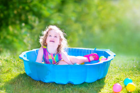 sandpit: Happy cute toddler girl with curly hair wearing a pink colorful dress playing in a sand box with plastic toy balls in a sunny green garden on a hot summer day