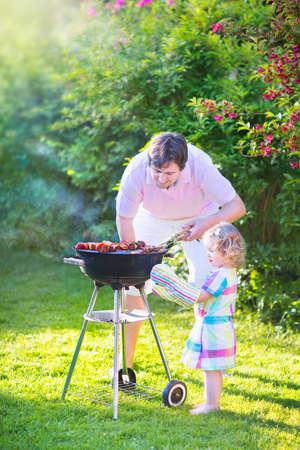 Junge liebevolle Vater und seine netten glücklichen Kleinkind Tochter, liebenswert lockiges Mädchen trägt ein buntes Kleid, zusammen Spaß Grillen von Fleisch und Gemüse in einem sonnigen Garten an einem heißen Sommertag