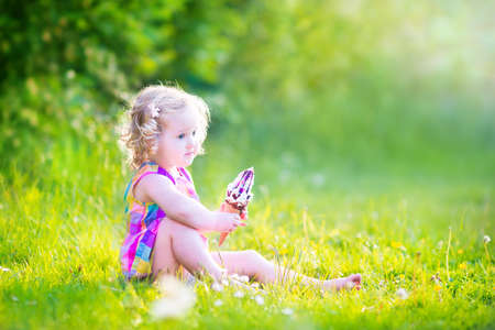 Funny happy toddler girl with curly hair wearing pink colorful summer dress sitting on a green lawn eating vanilla and chocolate ice cream cone in a sunny garden or park photo