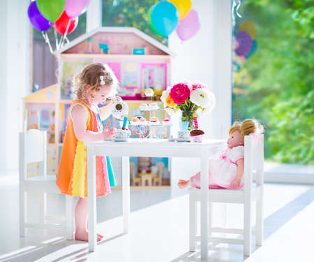 tea candles: Adorable toddler girl with curly hair wearing a colorful dress on her birthday playing tea party with a doll, toy dishes, cup cakes and muffins in a sunny room with window