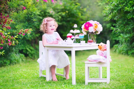 doll house: Adorable toddler girl with curly hair wearing a colorful dress on her birthday playing tea party with a teddy bear doll, toy dishes, cup cakes and muffins in a sunny summer garden Stock Photo