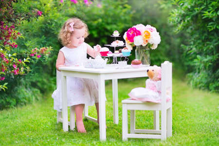 garden furniture: Adorable toddler girl with curly hair wearing a colorful dress on her birthday playing tea party with a teddy bear doll, toy dishes, cup cakes and muffins in a sunny summer garden Stock Photo
