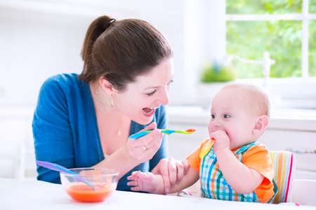 Young attractive mother feeding her cute baby son, giving him his first solid food, healthy vegetable pure from carrot with a plastic spoon sitting in a white sunny kitchen at a window photo