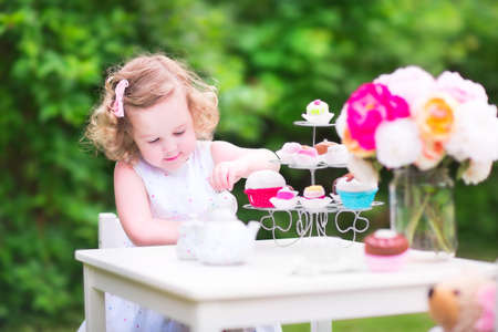 Adorable toddler girl with curly hair wearing a colorful dress on her birthday playing tea party with a teddy bear doll, toy dishes, cup cakes and muffins in a sunny summer garden Stock Photo