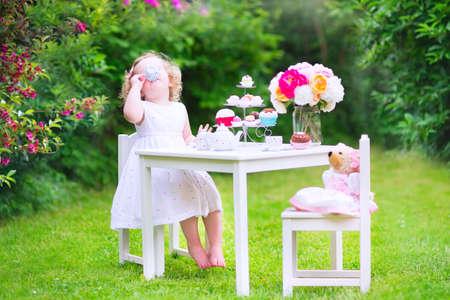 화창한 여름 정원에서 곰 인형, 장난감 요리, 컵 케이크, 머핀과 함께 그녀의 생일 재생 티 파티에 화려한 드레스를 입고 곱슬 머리를 가진 사랑스러운