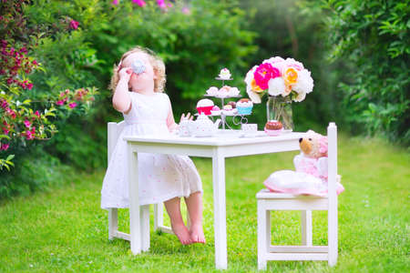 Adorable funny toddler girl with curly hair wearing a colorful dress on her birthday playing tea party with a teddy bear doll, toy dishes, cup cakes and muffins in a sunny summer garden photo