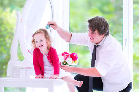Young happy father in a business suit and tie brushing the hair of his daughter, cute little curly toddler girl, sitting on a white dresser with a beautiful round mirror in a white bedroom with a big window photo