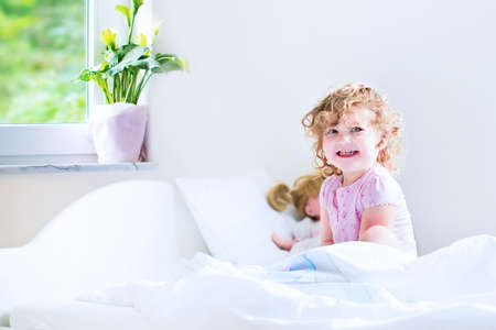 Funny curly toddler girl waking up on a early sunny morning in a white bedroom with window playing with her toys photo