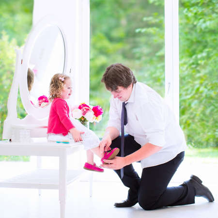 Young happy father in a business suit and tie helping his little daughter, cute curly toddler girl in a pink dress, to put on a shoe, at a white dresser with mirror in a bedroom with a big window photo