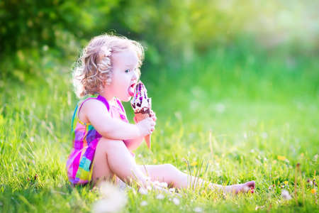 Funny happy toddler girl with curly hair wearing pink colorful summer dress sitting on a green lawn eating vanilla and chocolate ice cream cone in a sunny garden or park