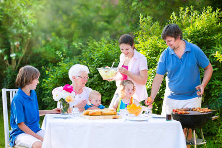 dinner party people: Happy big family - young mother and father with kids, teen age son, cute toddler daughter and a little baby, enjoying bbq lunch with grandmother eating grilled meat in the garden with salad and bread