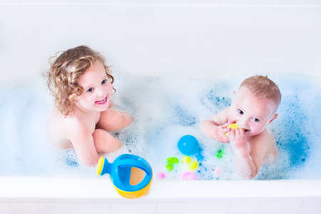 Funny little girl and her cute baby brother having fun taking bath together playing in water with foam with colorful toys after shower  photo