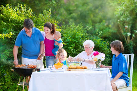 Happy big family - young mother and father with kids, teen age son, cute toddler daughter and a little baby, enjoying bbq lunch with grandmother eating grilled meat in the garden with salad and bread photo