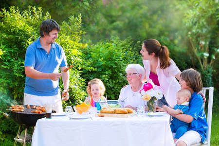 Happy big family - young mother and father with kids, teen age son, cute toddler daughter and a little baby, enjoying bbq lunch with grandmother eating grilled meat in the garden with salad and bread