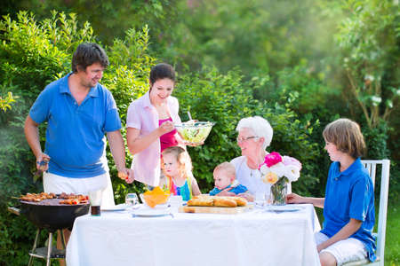 Happy big family - young mother and father with three kids, teen age son, cute toddler daughter and a little baby, enjoying bbq lunch with grandmother eating grilled meat in the garden with salad and bread photo