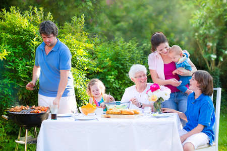 backyard: Happy big family - young mother and father with kids, teen age son, cute toddler daughter and a little baby, enjoying bbq lunch with grandmother eating grilled meat in the garden with salad and bread