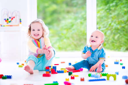 kids room: Adorable laughing toddler girl and a funny little baby boy, brother and sister, playing with colorful blocks sitting on a floor in a sunny bedroom with a big window  Stock Photo