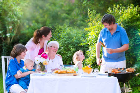 eating in the garden: Happy big family - young mother and father with kids, teen age son, cute toddler daughter and a little baby, enjoying bbq lunch with grandmother eating grilled meat in the garden with salad and bread
