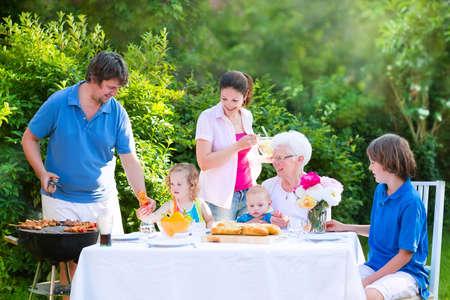 Gelukkig grote familie - jonge moeder en vader met kinderen, tiener leeftijd zoon, schattige peuter dochter en een kleine baby, genieten van bbq lunch met grootmoeder het eten van gegrild vlees in de tuin met salade en brood