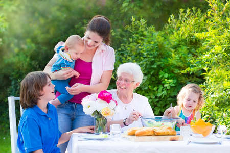 Happy grandmother enjoying a sunny summer day having lunch with her family - young woman and three children, teen age boy,cute curly toddler girl and a little baby, eatling grilled meat, salad and bread in the garden