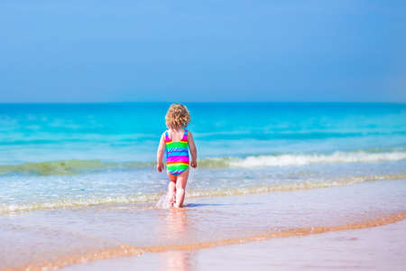 Happy curly little girl in colorful rainbow bathing suit running and playing on ocean coast in water splashes on beautiful tropical island beach with turquoise clear water having fun on vacation photo