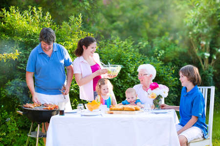 Happy adorable family - young mother and father with kids, teen age son, cute toddler daughter and a little baby, enjoying bbq lunch with grandmother eating grilled meat in the garden with salad and bread photo
