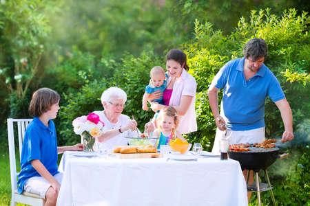 familia picnic: Gran familia feliz - joven madre y el padre con los niños, el hijo adolescente de la edad, hija lindo niño y un bebé, disfrutar de un almuerzo de barbacoa con la abuela de comer carne a la parrilla en el jardín con ensalada y pan