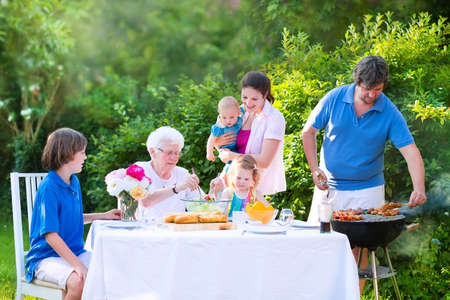 family picnic: Happy big family - young mother and father with kids, teen age son, cute toddler daughter and a little baby, enjoying bbq lunch with grandmother eating grilled meat in the garden with salad and bread