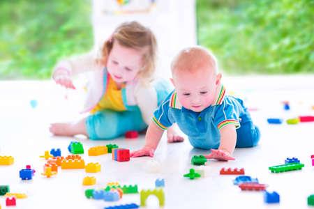 habitacion desordenada: Risa adorable niña pequeña y un poco de bebé divertido, hermano y hermana, jugando con bloques de colores sentado en un piso en una habitación soleada con una gran ventana