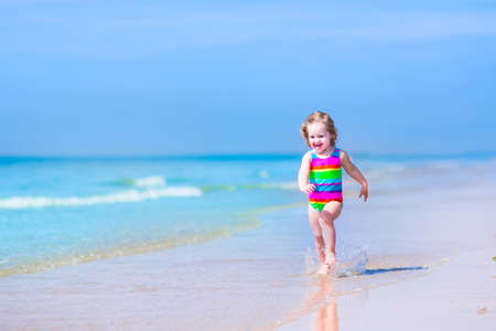 Happy laughing little girl in a colorful rainbow bathing suit runnig and playing on the ocean coast in water splashes on beautiful tropical island beach with turqouise clear water having fun on vacation photo
