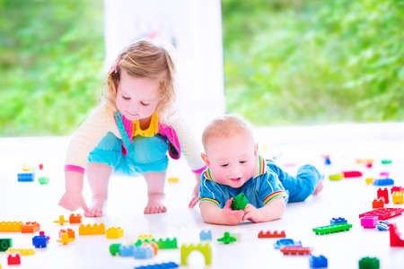 lego: Adorable laughing toddler girl and a funny little baby boy, brother and sister, playing with colorful blocks sitting on a floor in a sunny bedroom with a big window  Stock Photo