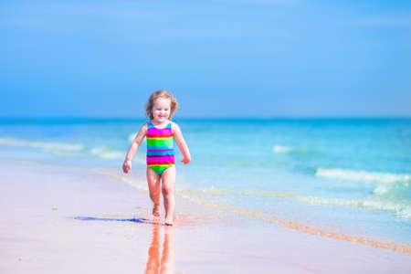 Happy laughing little girl in colorful rainbow bathing suit running and playing on ocean coast in water splashes on beautiful tropical island beach with turquoise clear water having fun on vacation photo
