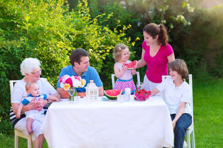 grand father: Happy big family - young mother and father with kids, teen age son, cute toddler daughter and a little baby, enjoying lunch with grandmother eating fruit, watermelon and strawberry in the garden Stock Photo