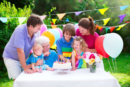 Happy big family - young parents, grandmother and three kids, teenage boy, toddler girl and little baby celebrating birthday party with cake and candles in the garden decorated with balloons and banners