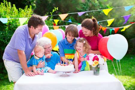 Heureux grande famille - jeunes parents, grand-mère et trois enfants, adolescent, enfant fille et petit bébé célébrer la fête d'anniversaire avec un gâteau et des bougies dans le jardin décoré avec des ballons et des banderoles