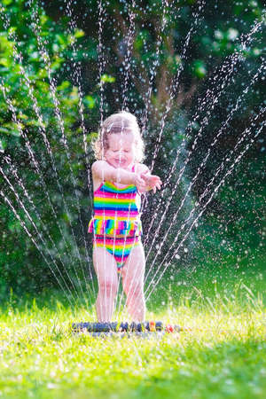 Funny laughing little girl in a colorful swimming suit running though garden sprinkler playing with water splashes having fun in the backyard on a sunny hot summer vacation day  photo