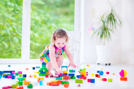 Adorable laughing toddler, cute little girl with curly hair wearing a pink summer dress, playing with colorful blocks and toys sitting on a floor in a sunny bedroom with a big window  photo