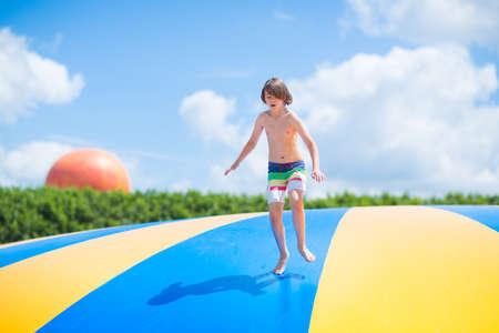 bungee jumping: Feliz niño riendo saltando en un trampolín colorido divirtiéndose en una fiesta en un parque de recreación durante las vacaciones de verano