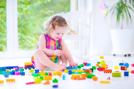 toddler playing: Adorable laughing toddler, cute little girl with curly hair wearing a pink summer dress, playing with colorful blocks and toys sitting on a floor in a sunny bedroom with a big window