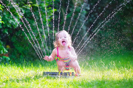 sprinkler: Funny laughing little girl in a colorful swimming suit running though garden sprinkler playing with water splashes having fun in the backyard on a sunny hot summer vacation day  Stock Photo