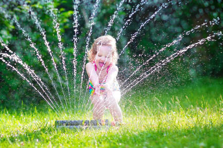 Funny laughing little girl in a colorful swimming suit running though garden sprinkler playing with water splashes having fun in the backyard on a sunny hot summer vacation day  Stock Photo