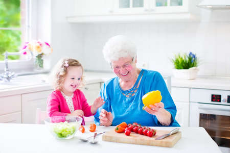 grandmother and children: Beautiful senior lady, happy loving grandmother making healthy salad for lunch with her granddaughter, cute curly little girl in a white sunny kitchen with window, cutting pepper and tomato
