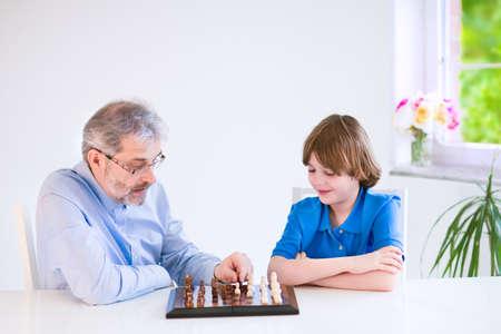 jugando ajedrez: Amoroso abuelo feliz que disfruta de un día con su nieto, riendo edad niño de la escuela, jugando al ajedrez en un comedor blanco con una ventana