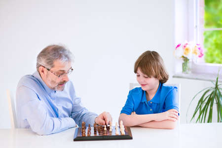 Happy loving grandfather enjoying a day with his grandson, laughing school age boy, playing chess in a white dining room with a window photo
