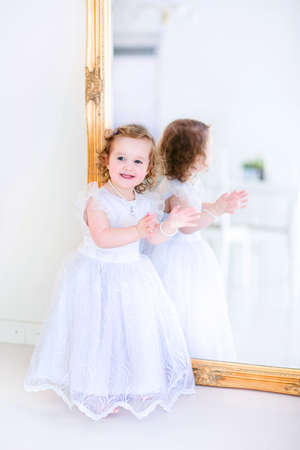 Sweet curly little girl with big beautiful eyes iwearing a white bridesmaid dress sitting at a big window playing princess in a sunny living room photo