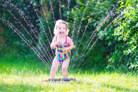 lawn sprinkler: Funny laughing little girl in a colorful swimming suit running though garden sprinkler playing with water splashes having fun in the backyard on a sunny hot summer vacation day
