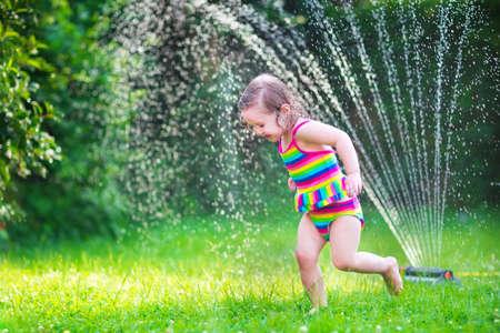 庭のスプリンクラー水と遊ぶことはね、裏庭で日当たりの良い夏の休暇日楽しんでをつうじてカラフルな水着で面白い笑っている小さな女の子 写真素材 - 31017421